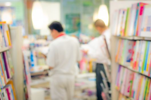 focused/Blur image of a bookstore with customers reading and looking for books. Bookstore background.