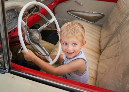Kid sitting on old American car 50s / 60s