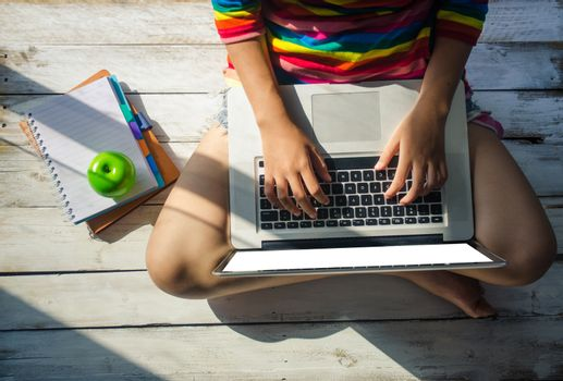 Young girls are using a laptop on a wooden floor. and sunshine