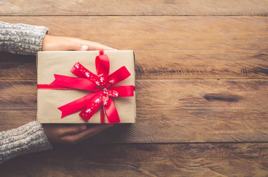 Woman holding gifts for special moments with special who on wood