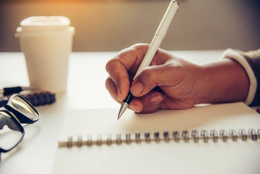 The woman's hands are writing note and coffee cup in open spect and light gold in morning