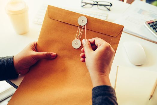Businessmen are about to open a brown envelope containing busine