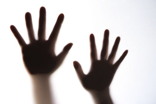 The silhouette of a woman's hand expressing fear.