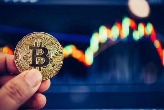 Bitcoin gold coins coin and defocused chart background