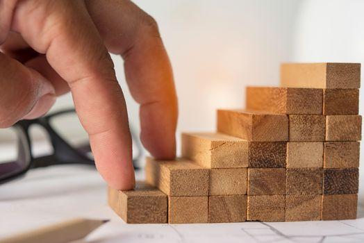 A hand that climbs on a wooden block - an effort concept.