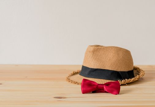 Hat and red bowtie are placed on wooden floor.