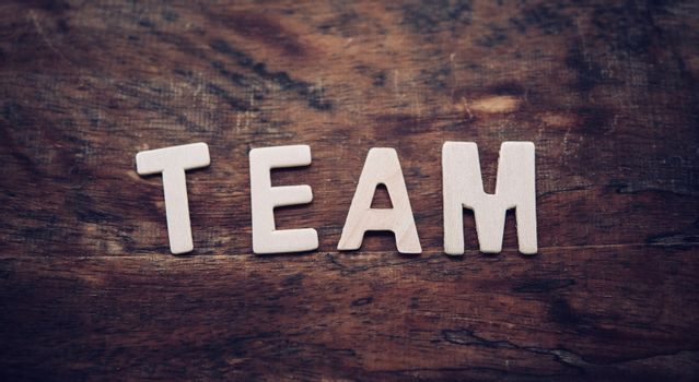 """The word """"TEAM"""" is arranged from a wooden letter placed on a woo"""