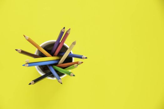 Stack of colored pencils in a glass on yellow background