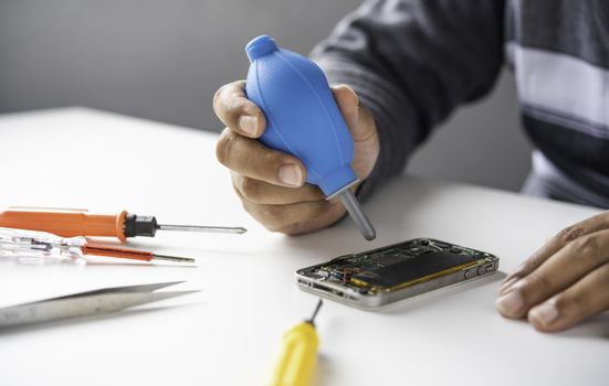Repairman disassembling Repairman disassembling smartphone with