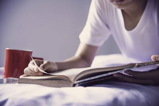 Teens read books on the bed in the bedroom.
