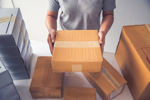 Hand holding closed-up tapes to pack products to prepare shipmen