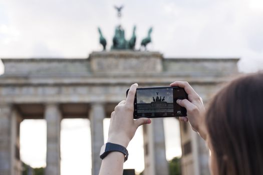 Hands holding phone mobile and takes pictures of Brandenburg Gat