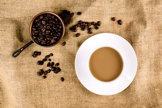 Coffee and coffee beans on a brown, structured background