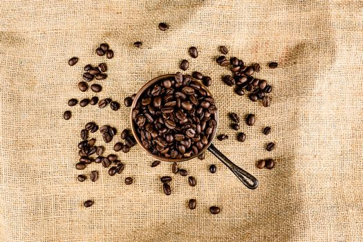 Coffee beans on brown, structured background
