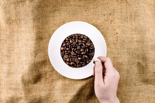 Hand reaching for a mug filled with coffee beans