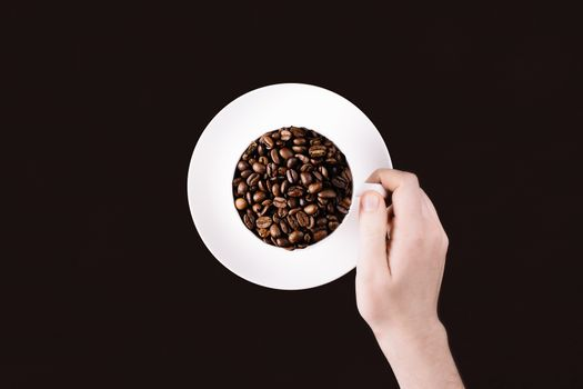 Hand reaching for a mug with coffee beans