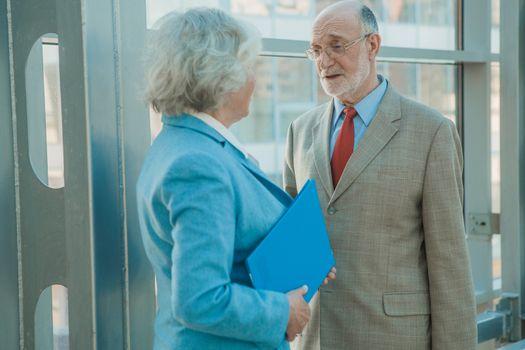 Senior business people discuss documents