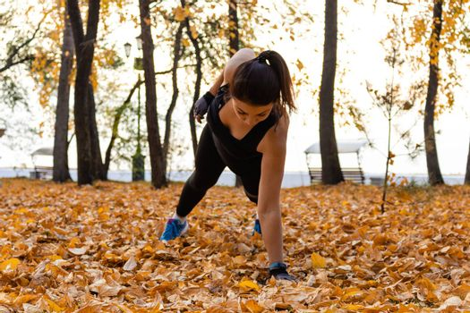 Attractive woman in sports clothes doing sports exercises in nature, on the carpet of autumn leaves, loves gymnastics, kneads his legs. Active young girl engaged in sports, leads a healthy lifestyle.