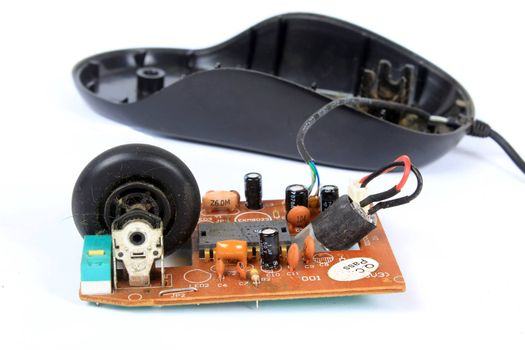 An old mouse with a wheel opened to show the technology used in it.