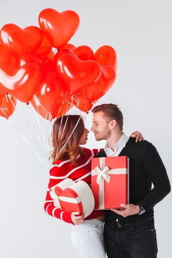 Happy kissing couple in love holding Valentines day gifts and bunch of heart shaped balloons