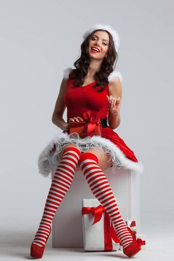 Beautiful young pin-up girl in santa dress unwrapping a christmas present