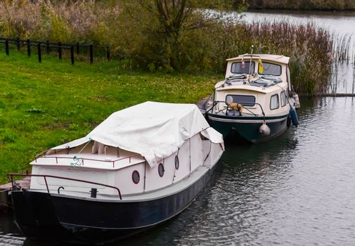 two typical dutch boats docked on the water shore, one covered u