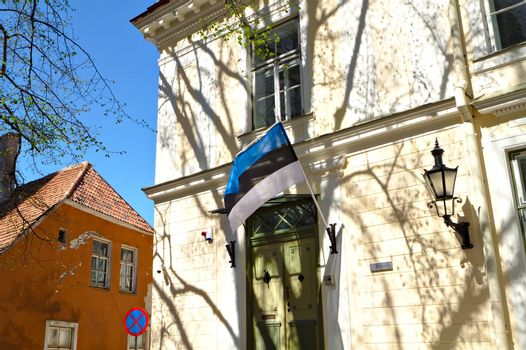 Estonian flag on the wall of a building in the Old Town Tallinn. Beige wall of an old building covered with shadows of a trees. Flag hanging next to the door.