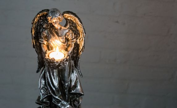 Christmas or spiritual tradition, a silver angel sculpture holding a burning light