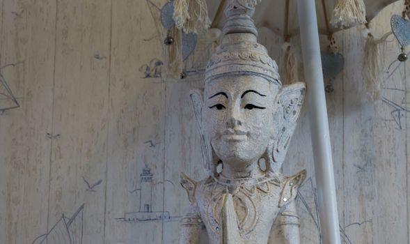 white buddha statue under a umbrella in closeup, a spiritual or buddhist background