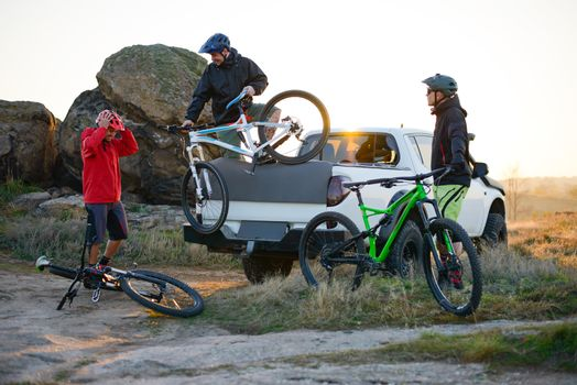 Friends Cyclists Getting Ready for Bike Riding and Taking the Bicycles off the Pickup Offroad Truck in the Mountains at Warm Autumn Sunset. MTB Adventure and Car Travel Concept.