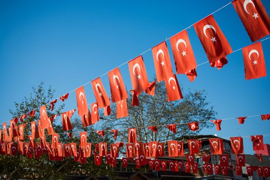 Turkish national flag hang on a pole on a rope in the street in open air