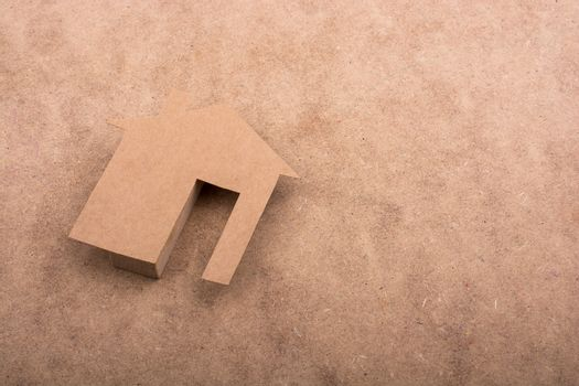 Little paper houses on a brown background