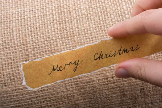 Merry Christmas wording written on a torn paper in hand
