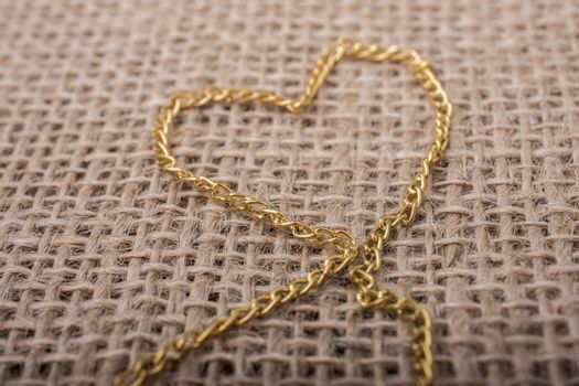 Heart shape formed out of gold color chain on canvas