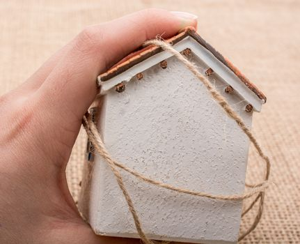 Thread wrapped around  a model house  on a brown background