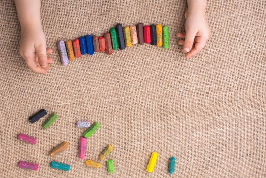 Toddlers hand putting crayons in line on canvas