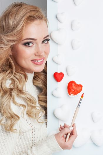 Beautiful young woman painting hearts with red paint