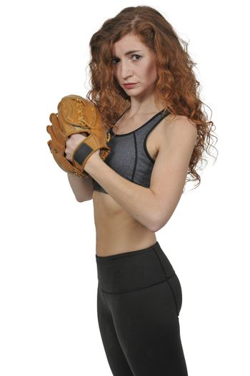 Beautiful woman baseball pitcher getting ready to throw a ball in a game