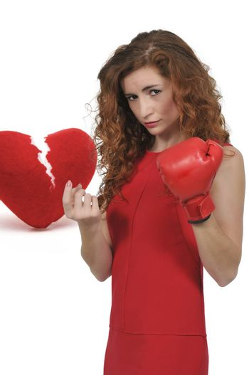 Beautiful woman in wearing a boxing glove in front of a broken heart - heartbreaker