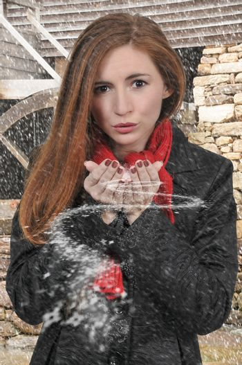 Beautiful woman blowing snow off of her hands