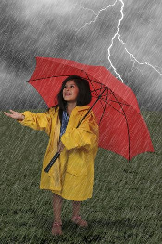 Little girl in a raincoat holding an umbrella in the rain