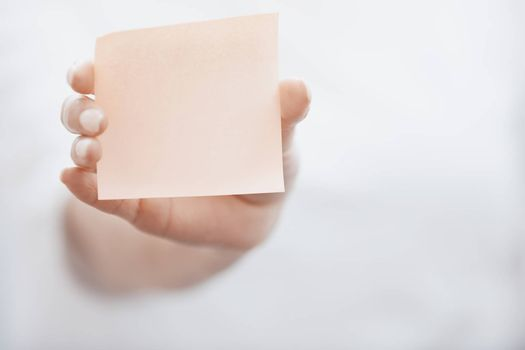 Human hand holding adhesive note