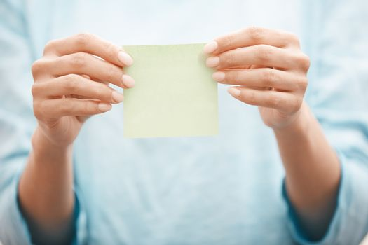 Woman holding adhesive note