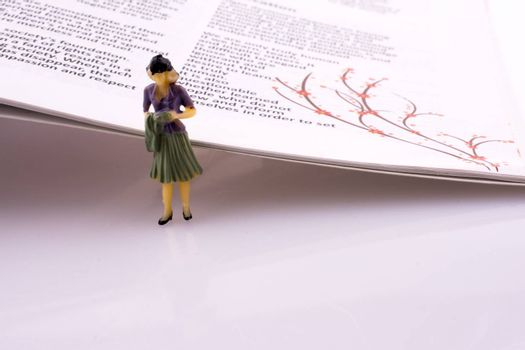 Little model woman figure standing by the side of the magazine pages