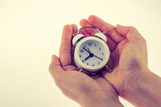 Child  holding an alarm clock  on white background