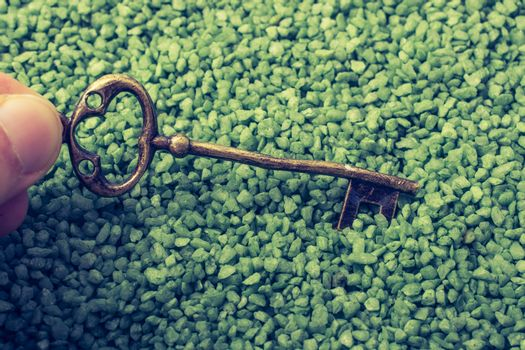 Hand holding retro style gold color key on green sand