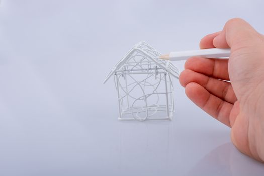 Little metal house and  a hand with a pencil