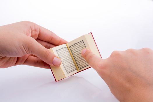 Hand holding The Holy Quran on a white background
