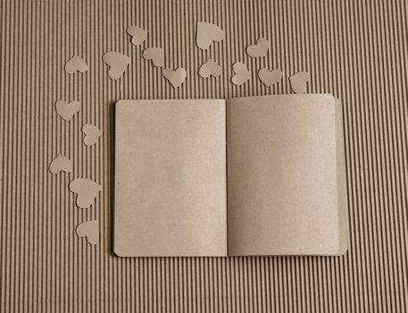 Paper hearts around notebook on cardboard
