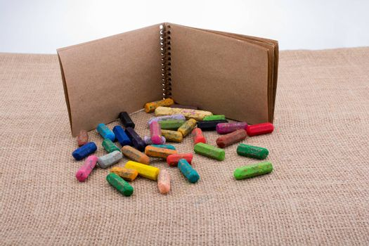 Notebook beside some colorful crayons